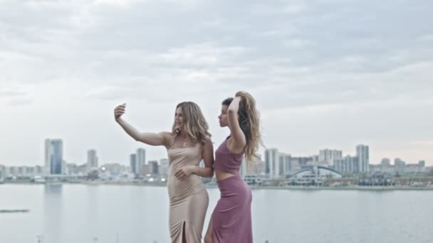 Two Attractive young women in party dresses on high hill having fun get a selfie by smartphone, wide shot