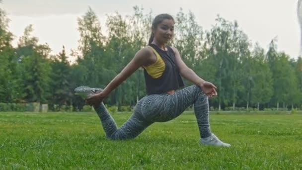 Mladý sport sexy fitness ženy dělají, flexibilní cvičení v parku, zblízka, dolly záběr