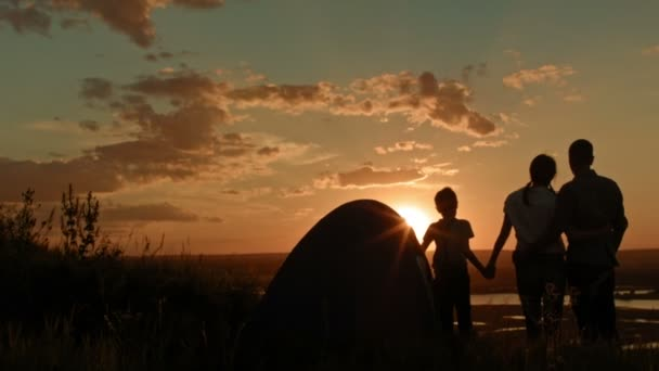 Young family - father, mother and son in camping - stands on high hill at summer sunset, looking for landscape, silhouette, wide angle