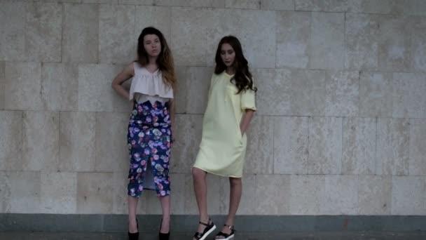 zwei attraktive junge Frauen posieren in Wandnähe für Modefotograf
