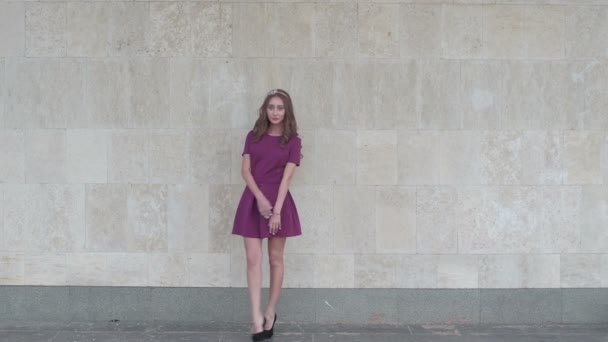 Mladá atraktivní žena pózuje u zdi pro módní fotograf