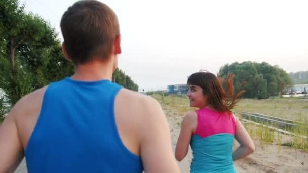 Několik mladých dospělých sportovců: žena a muž, běhání na promenádě. Koncept zdravého životního stylu, zpomalené