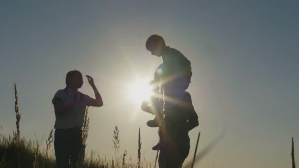Šťastná rodina na letní prázdniny - otec, matka a syn při západu slunce. Otec má syna v náručí, silueta