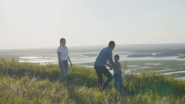 Happy Family on Summer Vacation - father, mother and son at sunset. having fun and walking along high hill
