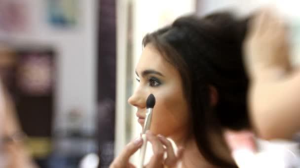 Smink művész szépség szalon teszi vonzó lány gyönyörű smink, fodrász teszi frizura, közelről