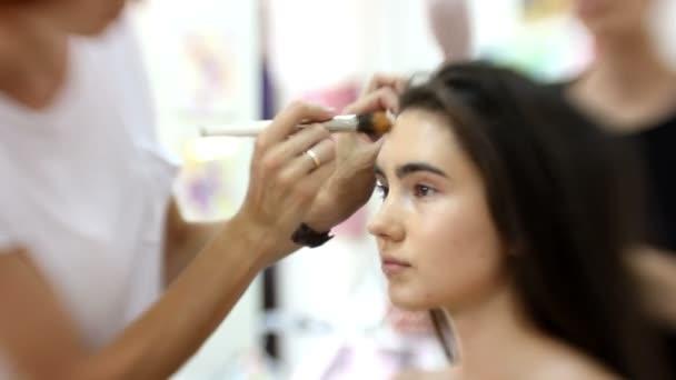 Smink művész teszi vonzó lány gyönyörű smink, fodrász teszi frizura: munka a bőr