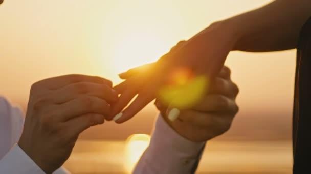 Anello di nozze messo sulle mani dito toccare tramonto sposa sposo uomo donna matrimonio proposta vacanza luna di miele