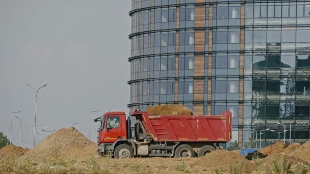 Stavební stroje pracující na staveništi: srovnávač načte písek do sklápěč