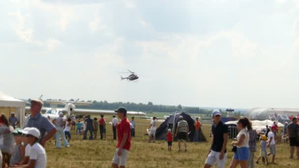 12 August 2016, Kazan, Russia - Kurkachi air show: the crowd at the festival looking at aerobatics planes - the helicopter is landing