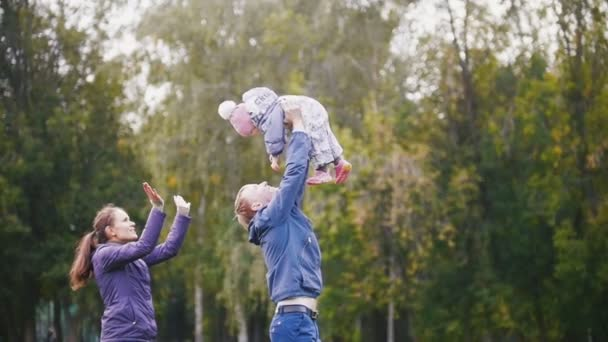 Happy family: Father, Mother and child - little girl walking in autumn park: dad holding a baby in hands, slow motion
