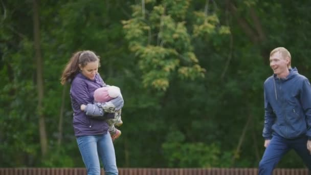 Happy family: Father, Mother and child - little girl walking in autumn park: mammy throws the baby in her arms