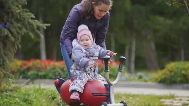 Šťastná rodina: otec, matka a dítě - holčičku v podzimním parku: Maminka a miminko hrát na hřišti