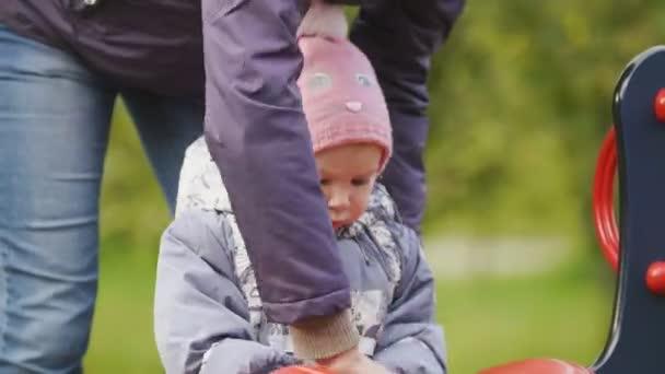 Šťastná rodina: otec, matka a dítě - holčičku v podzimním parku: matka a dítě hraje na hřišti, zblízka