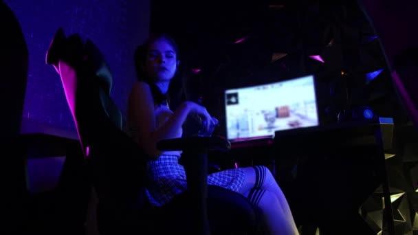 Fiatal szexi nő ül egy játékklubban, és játszik rágógumival a szájában