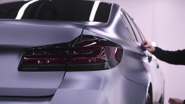 Auto-Detaillierung - Mann poliert die Oberfläche unter dem Türgriff eines grau und teuer aussehenden Autos