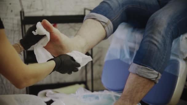 Pedikúra - mistr otírá nohy svého klienta po solné lázni