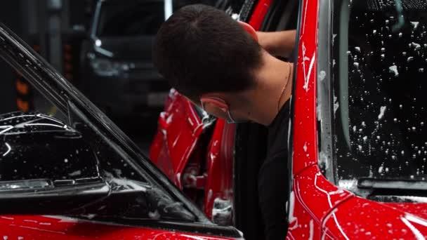 Autótisztítás - férfi munkás autóajtó mosása