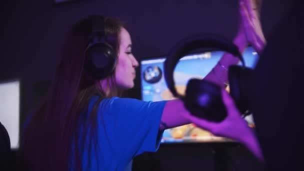 Eine junge Frau spielt mit ihren Freundinnen im Spielclub - und gibt ihren Freundinnen High Fives