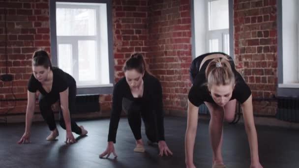 Stretching - három fiatal rugalmas nő támaszkodik a kezét, és felemeli az egyik lábát, majd felemeli a karját oldalra