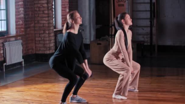 Dvě štíhlé ženy trénují společně v tělocvičně - dřepí s činkou