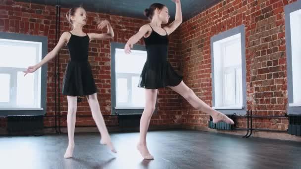 Balet tanec uvnitř - dvě malé gymnastika dívky synchronně tančí v černých šatech na tréninku
