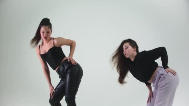 Dvě mladé stylové modelky tančící na cyclorama