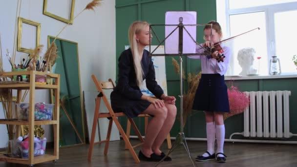 lekce houslí - malá holčička hrající na housle stojící ve třídě a její učitelka sedící vedle ní a upravující její pozici