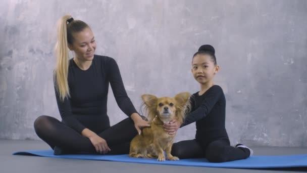 Kis torna ázsiai lány fekete test ruha tréner ül jóga mat és simogató kis gyömbér chihuahua kutya