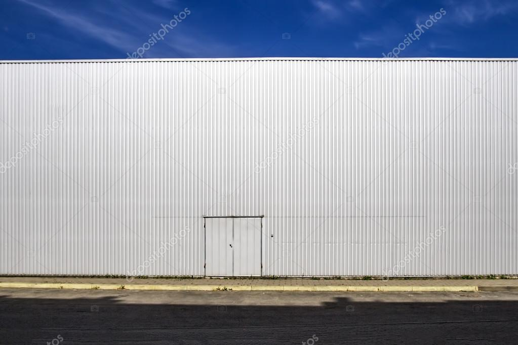 Corrugated sheet metal wall with a door the street shadows and blue sky. Outdoor & Corrugated sheet metal wall with a door the street shadows and blue ...