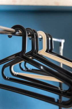 set of hangers on clothes rack, selective focus, blurred blue background