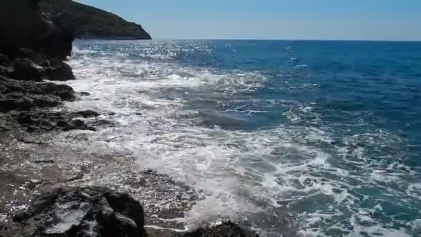 Palinuro, Campania, Olaszország - 2020. június 8.: Hullámok a kikötői öböl szikláin délután