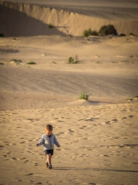 Little boy walking on the sand dunes