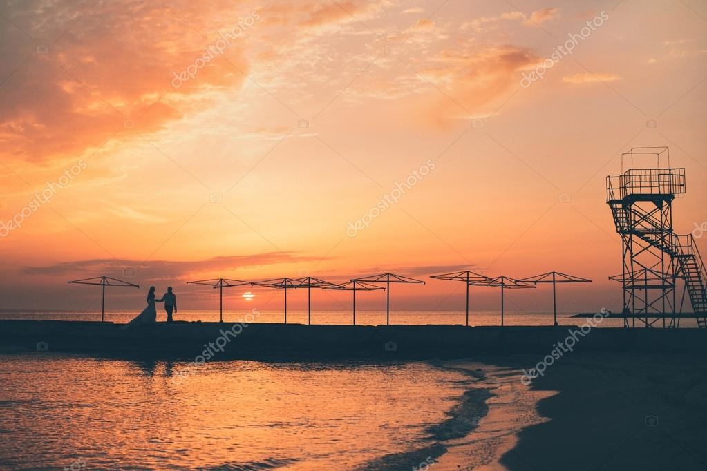 Bride and the groom against a sea sunset