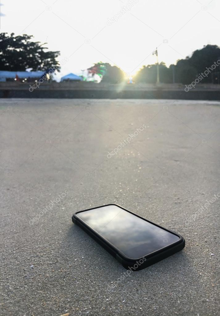 Smart phone lying on a sand of the clear beach with as light of sunset, it's mean stop social for relax