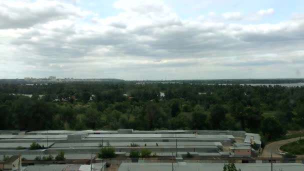 Timelapse of the sky with dark rain clouds. Strong wind before a thunderstorm on the outskirts of the city. Residential area with parking and garages near the river