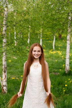 portrait of a beautiful red-haired girl in summer