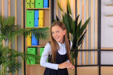 A child in a school uniform is posing in the classroom.