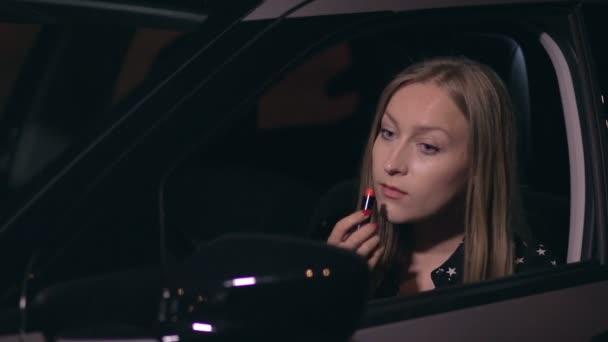 Pěkná řidička v autě dělá make-up