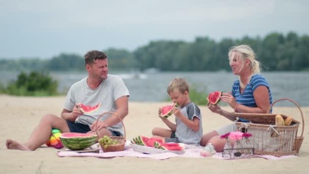 glückliche Familie isst Wassermelone am Strand