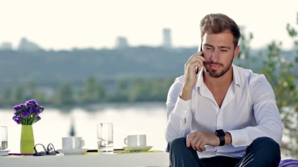 Schöner Mann telefoniert im Freien