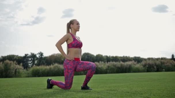 Slim atletické žena dělá čelní výpad a dřepy