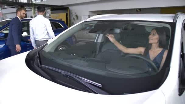 Muž a žena kupující testuje auta v autosalonu