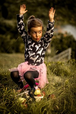 little girl playing on the grass in the daytime