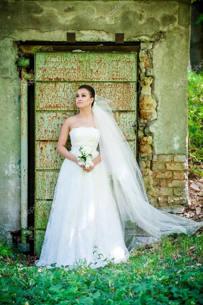 hermosa chica en vestido de novia junto a la puerta vieja — foto de