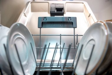 Close up of clean plates inside the dishwasher.