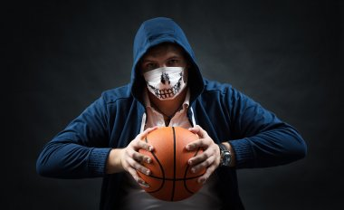 studio on a black background portrait of guy in mask with basketball