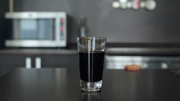 Little girl picks up a glass of juice and drink