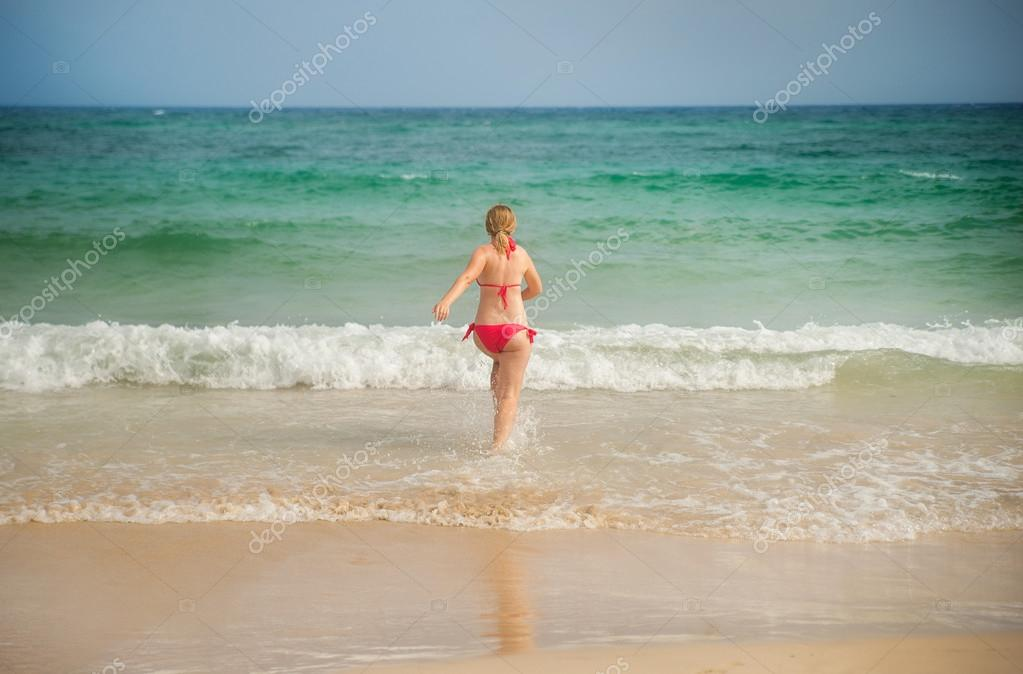 girl runs away in the sea view from the back
