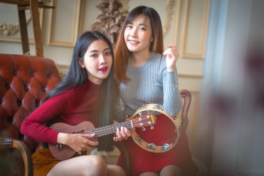 Two young girl friends having fun and smiling and Playing Guitar