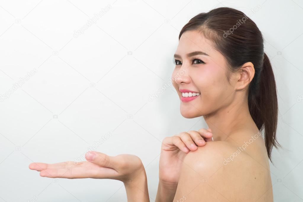 0af09240adb14 Mulher jovem e bonita com pele limpa saudável, apresentando alguma coisa —  Fotografia de Stock